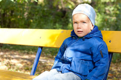 Little boy sitting on a yellow bench. Royalty Free Stock Photo