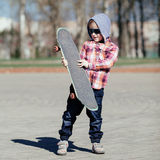 Little boy with skateboard on the street Stock Photography