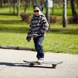 Little boy with skateboard on the street Stock Image