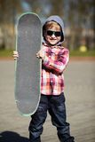Little boy with skateboard on the street Royalty Free Stock Image