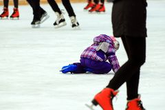 A little boy skates and falls on the ice in skate rink Active children and family sport, winter holidays. School sports clubs stock image