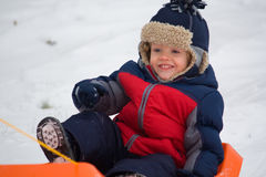 Little Boy on Sled. Cute Little Boy riding on a sled on a snowy hill Stock Images