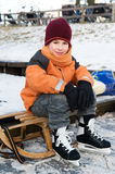 Little boy on a sled. Little boy resting on a sled after skating Royalty Free Stock Photography