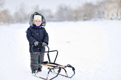 Little boy with sled in winter Stock Photo