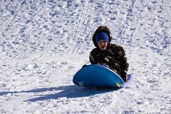 Little Boy Sledding abaixo do monte Foto de Stock Royalty Free