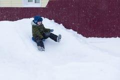 The little boy sledding with snow slides. Little boy in winter clothes sledding with snow slides Royalty Free Stock Photos
