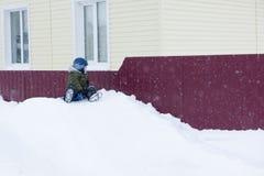 The little boy sledding with snow slides. Little boy in winter clothes sledding with snow slides Stock Photos