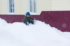 The little boy sledding with snow slides Stock Photography
