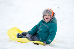 Little boy sledding. On snowy background showing tongue Stock Photo