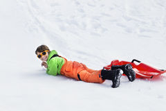 Little boy sledding very fast and falls on the snow Stock Photo