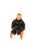 Little boy on the sledge Stock Photos