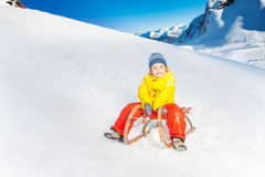 Little boy on the sledge slide down hill Stock Photos
