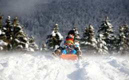 A little boy sledging in the snow Stock Photography