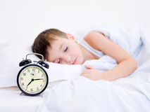 Little boy sleeping with alarm clock Royalty Free Stock Photo