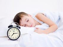 Little boy sleeping with alarm clock Royalty Free Stock Photo
