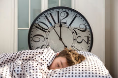 Little boy sleeping with alarm clock stock image