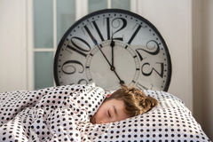 Little boy sleeping with alarm clock stock photos