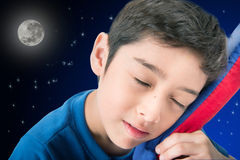 Little boy sleeping in bed with night background Stock Photos