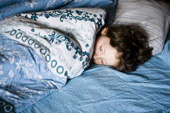 Little boy sleeping in bed Stock Image