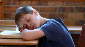 Little boy sleeping on a book in classroom Royalty Free Stock Image