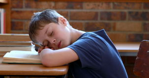 Little boy sleeping on a book in classroom stock footage