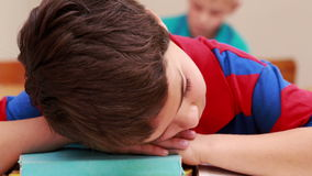 Little boy sleeping on a book in classroom. At the elementary school stock video footage