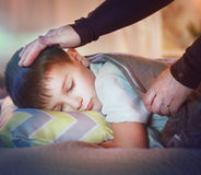Little boy sleeping and dreaming in his bed. Mother cover her little son with a blanket Royalty Free Stock Photography