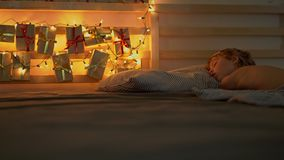 A little boy sleeping in his bed with an advent calendar lighten with Christmas lights shines on a back of his bed. Getting ready for Christmas and New Year stock video footage