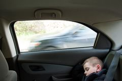 Little boy sleeping inside car near window with passing car behind Royalty Free Stock Photo