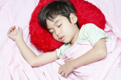 Little boy sleeping at night. On the bed red pillow Royalty Free Stock Photography