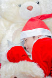 Little boy sleeping on santa dress with the big bear Stock Photo