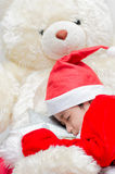 Little boy sleeping on santa dress with the big bear Stock Photography