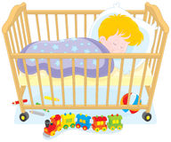 Little boy sleeping. Small boy sleeps in his bed in a kids bedroom with toys Royalty Free Stock Photography