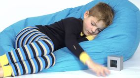 Little boy turn off alarm clock during sleeping. Little boy sleeps at bean bag at white background. Sound of alarm clock wakes the child. Cute kid with closing stock footage