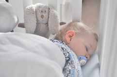 The little boy sleeps with a pacifier. In the bed Stock Photography