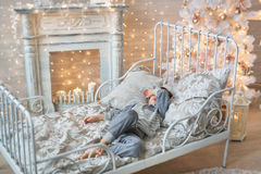 Little boy sleeps in a room with Christmas tree. A little boy sleeps on a bed in a room with Christmas tree and a fireplace Stock Photography
