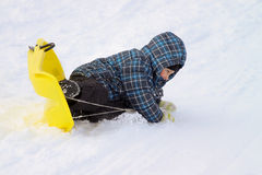 Little boy on sleigh doing an overturn Stock Photography