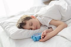 Little boy sleping in white bed with alarm clock near his head Stock Image