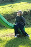 Little boy on a slide. Little boy sitting on a green slide royalty free stock images