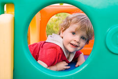 Little Boy on Slide. Toddler Boy playing on a slide Royalty Free Stock Photo