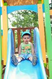 Little boy on a slide. Little boy on a blue slide Royalty Free Stock Image