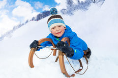 Little boy slide down laying on sledge smile stock photo