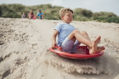 Little Boy Sliding Down a Sand Dune Royalty Free Stock Images
