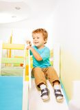 Little boy sliding from slide Stock Photos