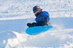 Winter fun - Boy sliding Royalty Free Stock Photography