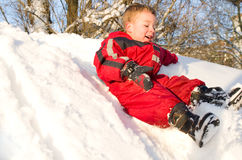 Little boy sliding in the snow Royalty Free Stock Images