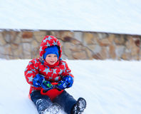 Little boy sliding in snow Royalty Free Stock Photo