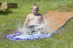 Little boy sliding on a water slide Royalty Free Stock Image