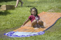 Little boy sliding on a water slide Stock Photo