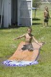 Little boy sliding on a water slide Stock Photo